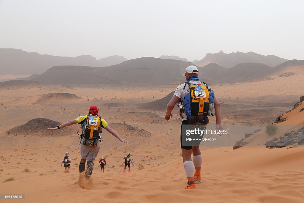 Competitors cross the sandy Mziouda valley, on April 9, 2013, during the third stage of the 28th edition of the 'Marathon des Sables', some 300 Kilometers, South of Ouarzazate in Morocco. The Desert Marathon is considered as the hardest in the World. About 1024 participants have to walk all along 223,8 Kms during 7 days in the Moroccan Sahara in self food sufficient. AFP PHOTO/PIERRE VERDY