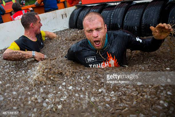 Competitors dive in an ice filled bath of muddy water while challenging in Tough Mudder endurance race in HenleyonThames England on 27 April 2014...