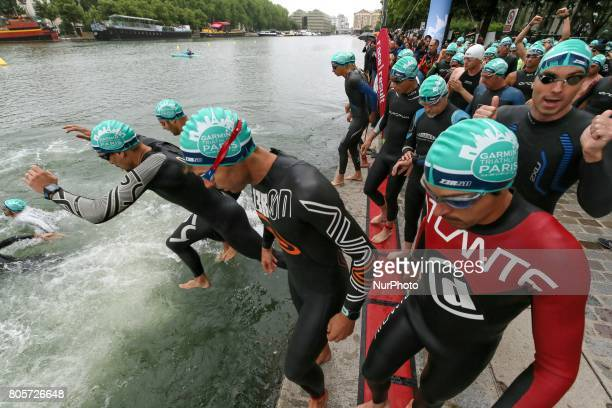 Competitors dive in the Bassin de La Villette during the swim section of the 2017 edition of the Paris triathlon on July 2 2017 in Paris An...