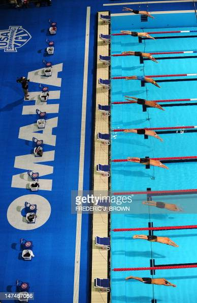 Competitors dive into the pool to start their race in the Heat 17 of the men's 50M freestyle event on day six of the 2012 US Olympic Team Trials on...