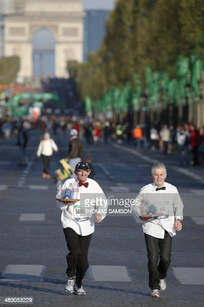 Competitors dressed as waiter run on the Champs Elysees at the start of the 38th Paris Marathon on April 6 2014 in Paris AFP PHOTO / THOMAS SAMSON