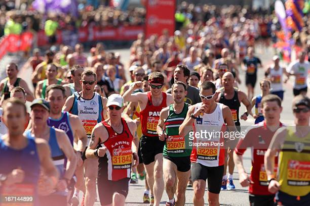 Competitors emerge from Tower Bridge during the Virgin London Marathon on April 21 2013 in LONDON ENGLAND