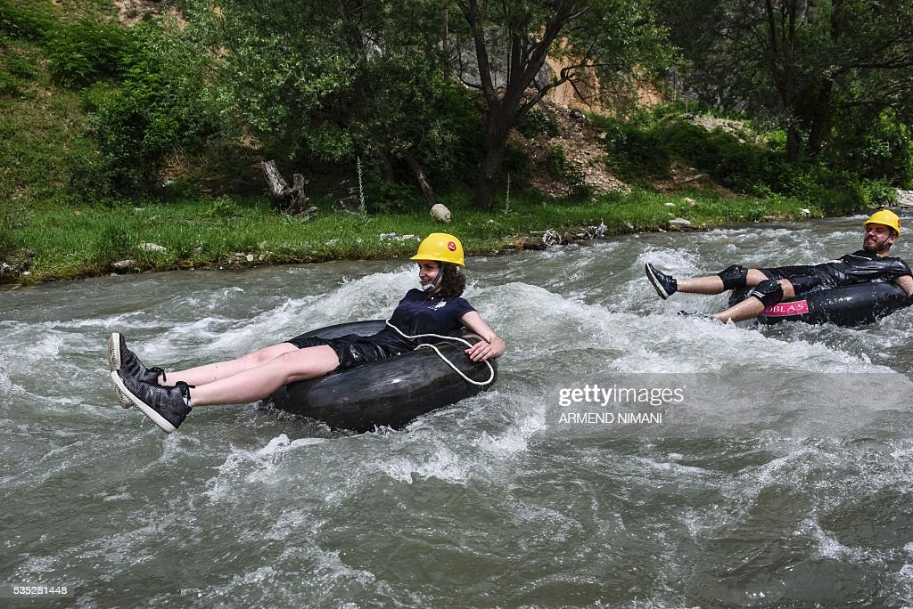Competitors floant on tranctor inner tubes during an anlternantive sport rubber competition titled 'Bunanr Fest' on Many 29, 2016 on the Bistrican river in the southern Kosovo town of Prizren. / AFP / ARMEND