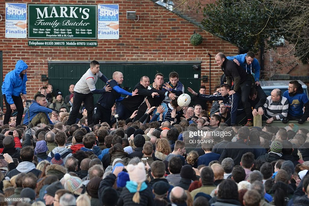 Competitors from the opposing teams, the Up'ards and the Down'ards, reach for the ball during the annual Royal Shrovetide Football Match in Ashbourne, northern England, on February 9, 2016. The mass-participation ball game involves two teams, whose players are defined by which side of a small brook that bisects the town they were born, aiming to score a goal, which are some three miles apart. The game, which has very few rules, is played over two 8 hour periods on Shrove Tuesday and Ash Wednesday. Royal Shrovetide Football is believed to have been played annually in Ashbourne since 1667. / AFP / OLI SCARFF