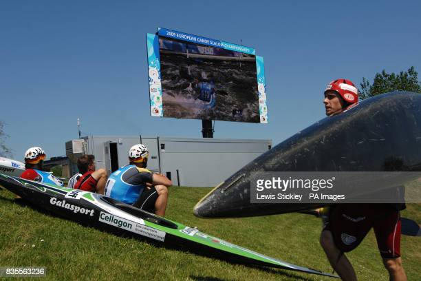 K1 competitors Germany's Sebastian Schubert and Alexander Grimm watch their opponent Fance's Boris Neveu on the giant screen