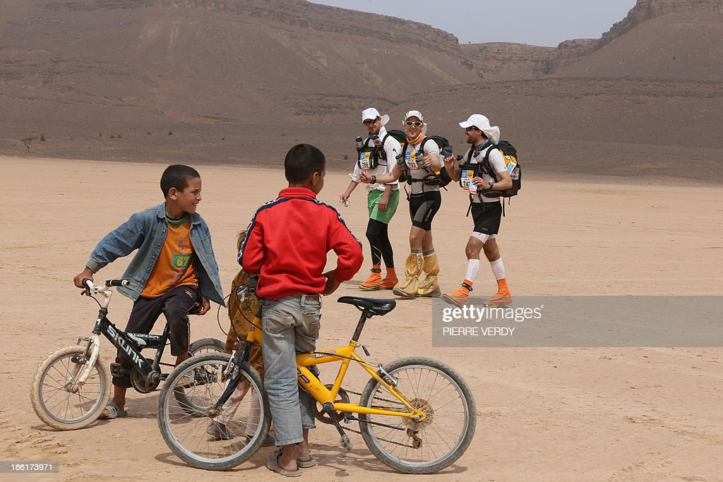 Competitors greet children as they cross a dried-out lake, on April 9, 2013, during the third stage of the 28th edition of the 'Marathon des Sables', some 300 Kilometers, South of Ouarzazate in Morocco. The Desert Marathon is considered as the hardest in the World. About 1024 participants have to walk all along 223,8 Kms during 7 days in the Moroccan Sahara in self food sufficient.