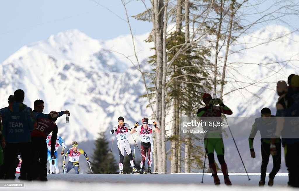 Competitors head through for a feed station duringThe Men's 50km Mass Start Free on Day 16 of the Sochi 2014 Winter Olympics at Laura Cross-country Ski & Biathlon Center on February 23, 2014 in Sochi, Russia.