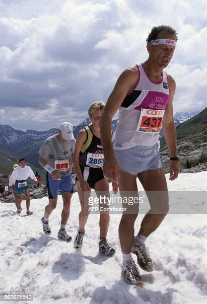 Competitors in the 16th edition of the Swiss Alpine marathon pass a snow field in the region of the Scalettapass near Davos Switzerland 28 July 2001...