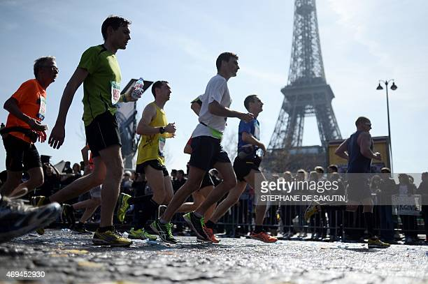 Competitors in the 39th Paris Marathon runs past the Eiffel Tower in Paris on April 12 2015 Mark Korir of Kenya won the Paris Marathon his first...