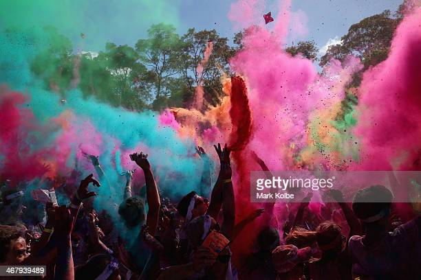 Competitors listen to a DJ set and throw packets of coloured powder after finishing the Color Run at Sydney Olympic Park on February 9 2014 in Sydney...