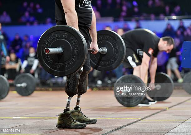 TOPSHOT Competitors make exercises as they take part in the final competition for CrossFit Games called 'Games of the Heroes' in Kiev on December 24...