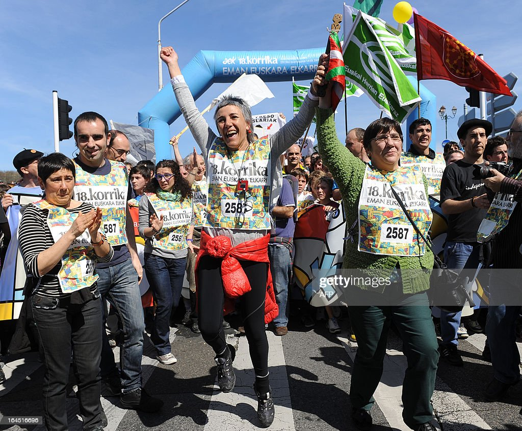 Competitors of the 18th Korrika, a 10 day relay race aimed at raising funds for the teaching of the Basque language, are pictured after crossing the finish line, on March 24, 2013 in Bayonne, south western France.