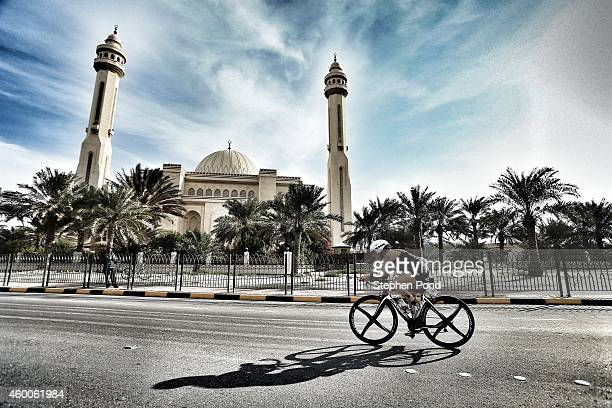 Competitors on the bike leg pass with AlFateh Grand Mosque during the Challenge Triathlon Bahrain on December 06 2014 in Bahrain Bahrain