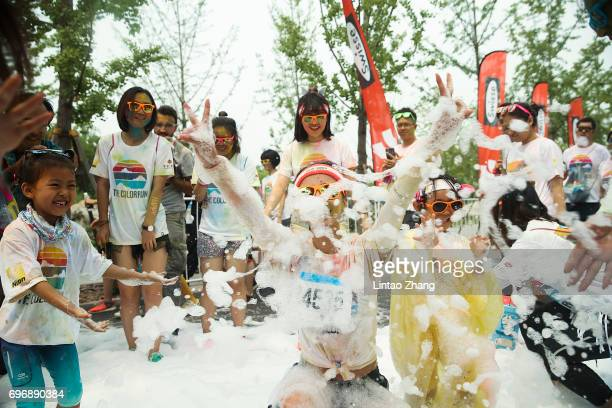 Competitors playing with soap bubbles during the Colour Run at the Beijing International Garden Expo park on June 17 2017 in Beijing China