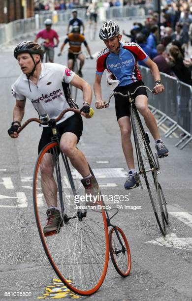 Competitors race penny farthing bicycles around Smithfield Market London as part of the The IG London Nocturne cycle event