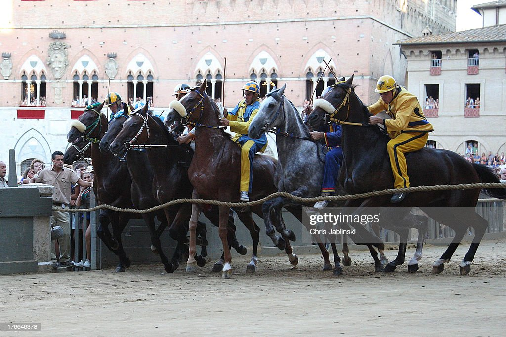 Competitors race riding bareback during the annual Palio dell'Assunta horse-race at the Piazza del Campo Square on August 16, 2013 in Siena, Italy. The Palio races in Siena, in which riders representing city districts compete, and takes place twice a year in the summer in a tradition that dates back to 1656.