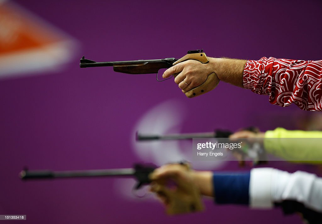 Competitors raise their pistols during the Mixed P450m PistolSH1 competition on day 8 of the London 2012 Paralympic Games at The Royal Artillery...