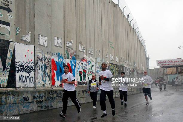 Competitors run along the separation barrier during the first marathon in the West Bank town of Bethlehem on April 21 2013 The race which begins at...