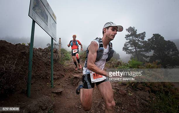 Competitors run down a track though foggy vineyards in the Caldera de Taburiente National Park during the Transvulcania ultra trail event on May 7...