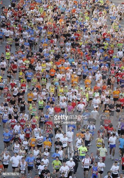 Competitors run on Maria Cristina avenue near the Espaa square during the marathon race in Barcelona on March 2 2008 More than nine thousand runners...