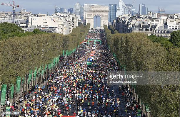 Competitors run on the Champs Elysees at the start of the 38th edition of the Paris Marathon on April 6 2014 in Paris AFP PHOTO / THOMAS SAMSON