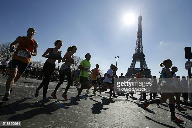 Competitors run past the Eiffel Tower during the 40th Paris Marathon on April 3 2016 in Paris Some 57000 participants from 160 countries have...