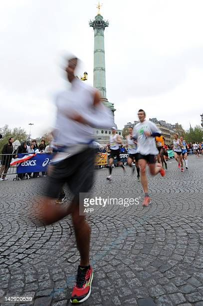 Competitors run past the July Column on the Bastille square during the 36th Paris Marathon on April 15 2012 AFP PHOTO / BERTRAND LANGLOIS