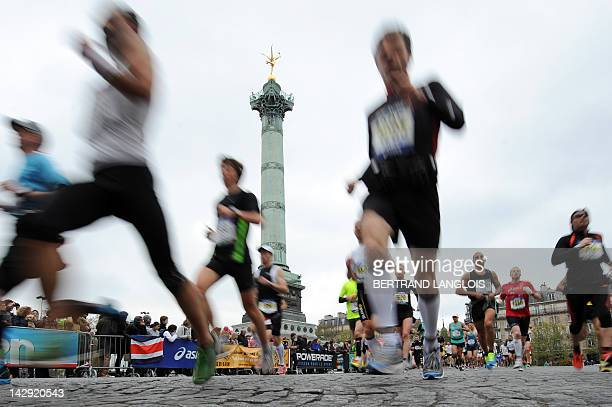 Competitors run past the July Column on the Bastille square during the 36th Paris Marathon on April 15 2012 in Paris AFP PHOTO / BERTRAND LANGLOIS