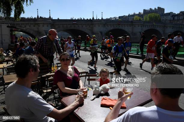 Competitors run past the PontNeuf as people enjoy the sun on a cafe terrace during the 41st Paris Marathon in Paris on April 9 2017 / AFP PHOTO /...