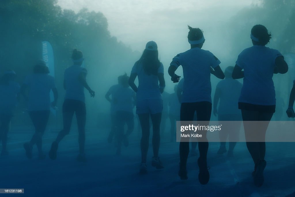 Competitors run through the blue colour throw during the Colour Run at Sydney Olympic Park on February 10, 2013 in Sydney, Australia.