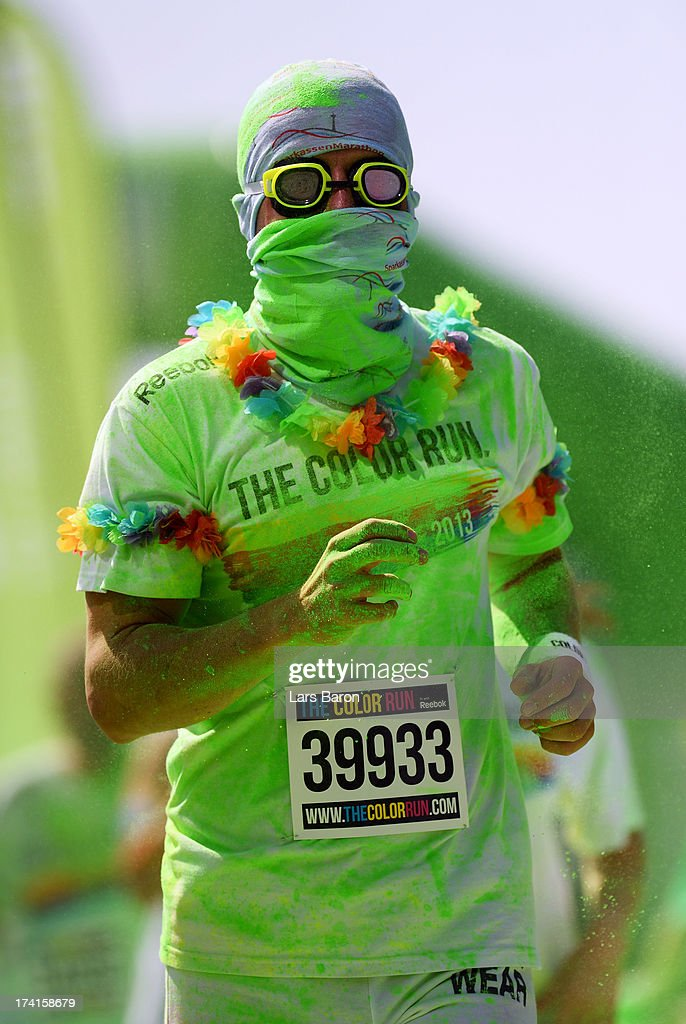 Competitors run through the green colour throw area during the Color Run on July 21, 2013 in Cologne, Germany.