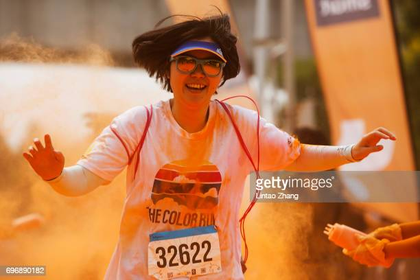 Competitors run through the orange colour station during the Colour Run at the Beijing International Garden Expo park on June 17 2017 in Beijing China