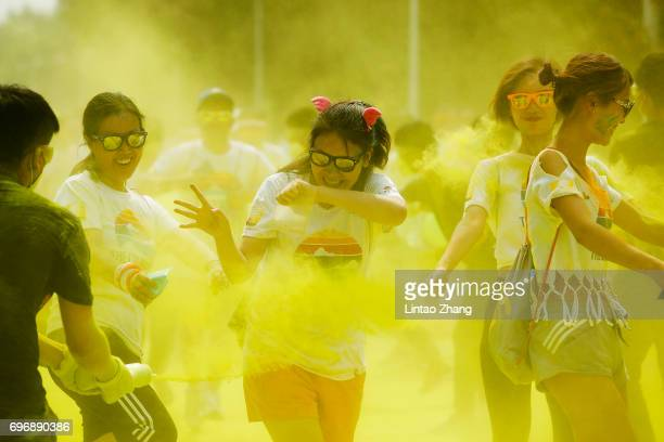 Competitors run through the yellow colour station during the Colour Run at the Beijing International Garden Expo park on June 17 2017 in Beijing China