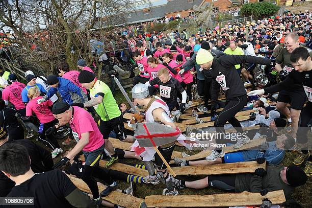 Competitors run to the start line over other race runners before the Tough Guy race on January 30 2011 in Perton near Wolverhampton England Thousands...