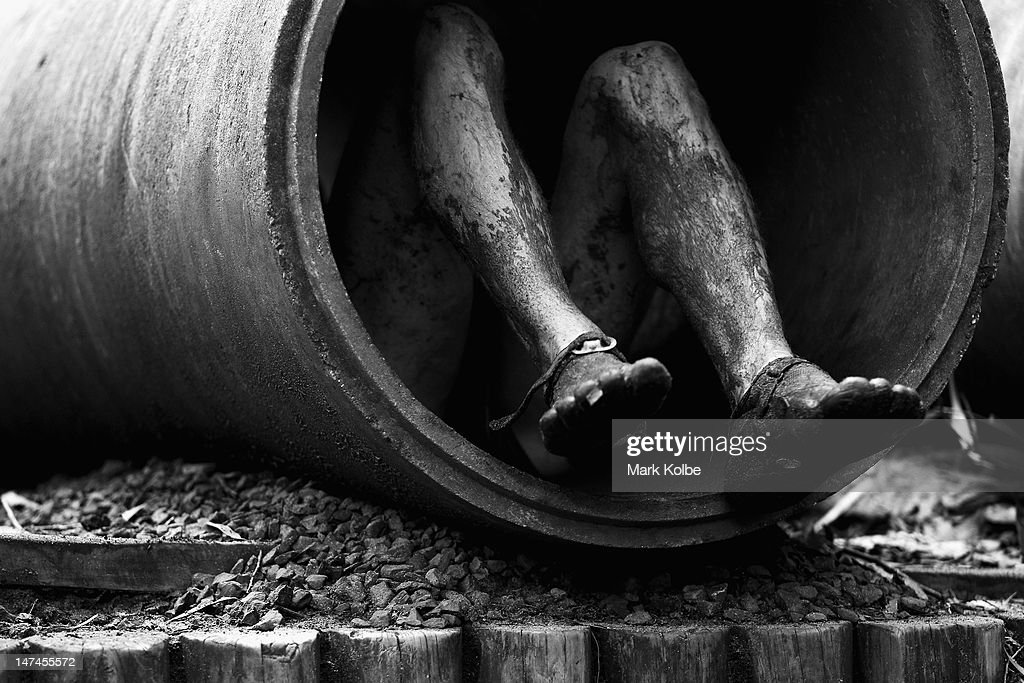 A competitors shoes are seen as he crawls through a concrete pipe in the 'Plumber's Crack' obstacle as he competes in the Tough Bloke Challenge at the Cataract Scout Park on June 30, 2012 in Sydney, Australia.