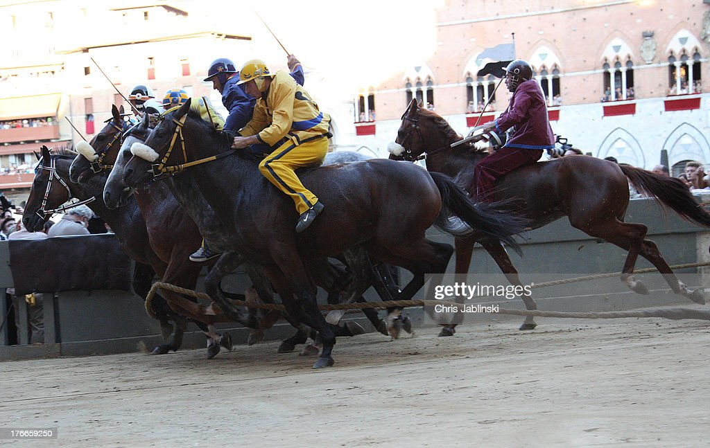 Competitors start off across the Piazza del Campo square during the annual Palio dell'Assunta horse-race on August 16, 2013 in Siena, Italy. The Palio races in Siena, in which riders representing city districts compete,and takes place twice a year in the summer in a tradition that dates back to 1656.