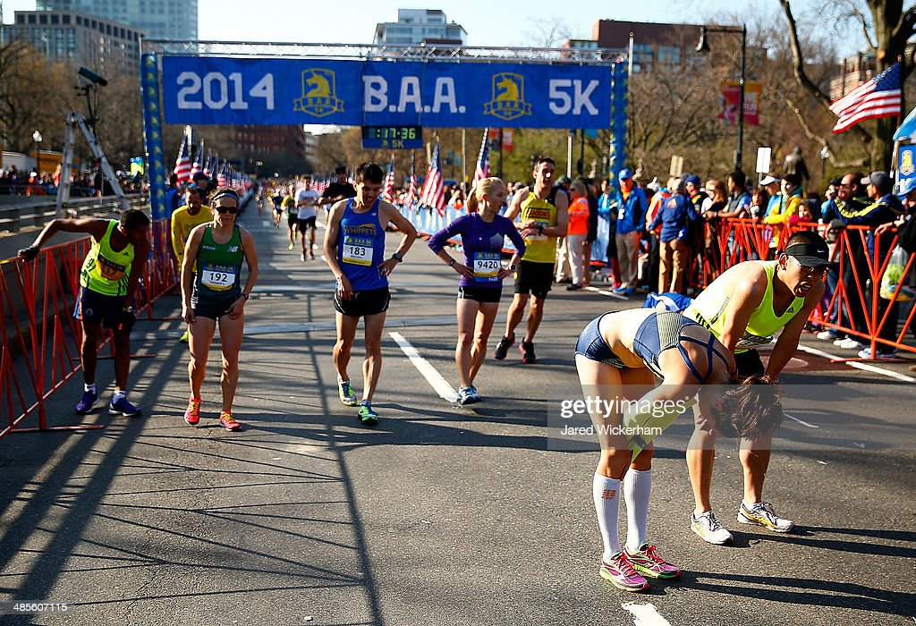 Competitors stop after running in the 2014 B.A.A. 5K on April 19, 2014 in Boston, Massachusetts.