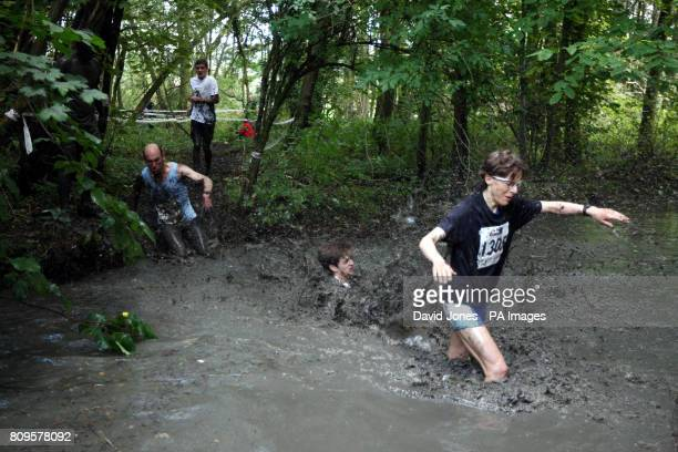 Competitors struggle through the mud on the 7 mile course through the grounds of Eastnor Estate in Herefordshire during the Mud Runner Adventure