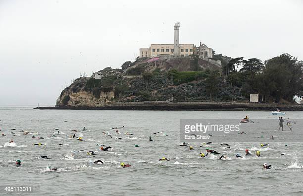 Competitors swim past Alcatraz at the start of the 2014 Escape from Alcatraz Triathlon on June 1 2014 in San Francisco California