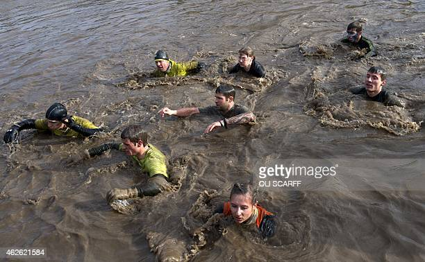 Competitors swim through muddy water as they take part in the 'Tough Guy' adventure race near Wolverhampton Staffordshire West Midlands on February 1...