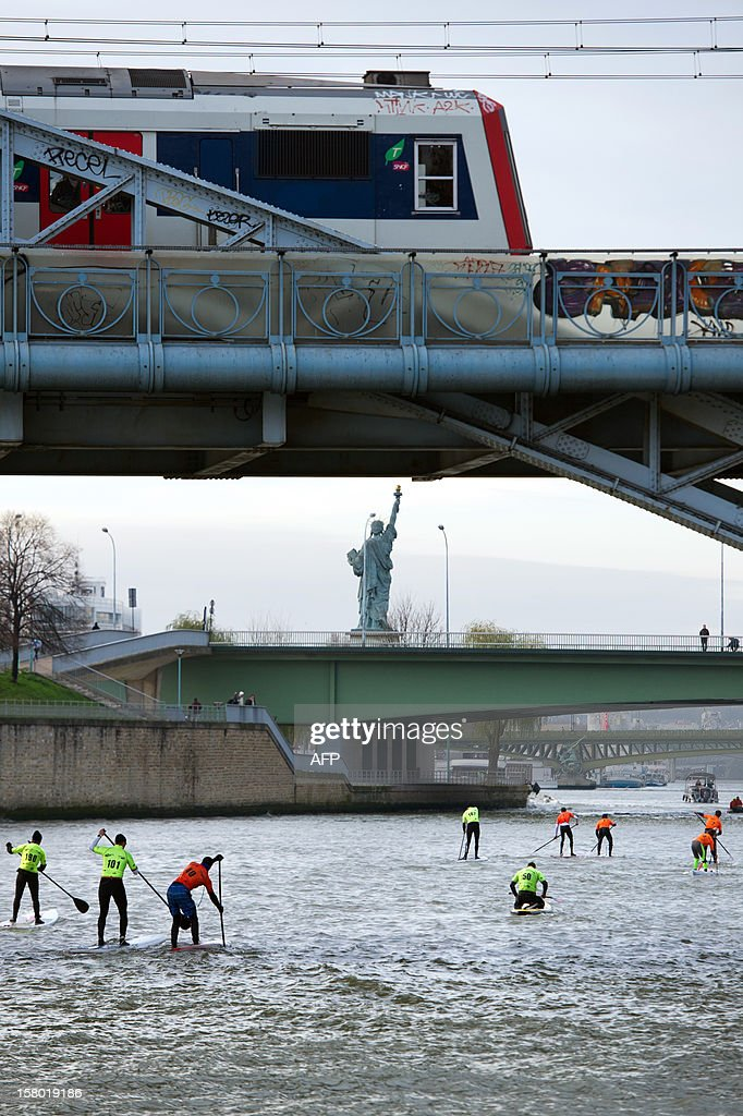 Competitors take part in a stand up paddle race on the Seine river in Paris as a train drives on a bridge, on December 9, 2012. This event is part of the 52nd Paris International Boat Show (Salon nautique). At background, a copy of the 'Liberty statue',, a work of French Auguste Bartholdi. AFP PHOTO BERTRAND LANGLOIS