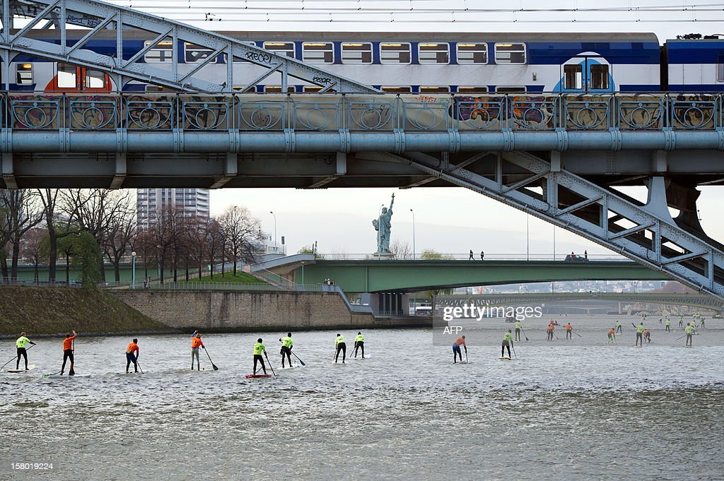 Competitors take part in a stand up paddle race on the Seine river in Paris as a train drives on a bridge, on December 9, 2012. This event is part of the 52nd Paris International Boat Show (Salon nautique). At background, a copy of the 'Liberty statue', a work of French Auguste Bartholdi.