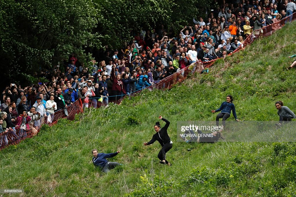 Competitors tumble down Cooper's Hill in pursuit of a round Double Gloucester cheese during the annual Cooper's Hill cheese rolling competition near the village of Brockworth, Gloucester, in western England, on May 30, 2016. The annual Cooper's Hill Cheese Rolling involves hordes of fearless competitors chasing an eight pound Double Gloucester cheese down a steep hill. The slope has a gradient in places of 1-in-2 and in others 1-in-1, its surface is very rough and uneven and it is almost impossible to remain on foot for the descent. The winner of the downhill race wins the cheese. / AFP / ADRIAN