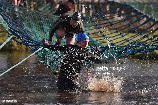 Competitors wade through water during the annual Tough Guy Challenge race on February 1 2015 in Telford England