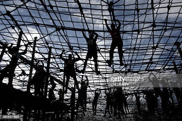 Competitors walk on ropes as they take part in the 'Tough Guy' adventure race near Wolverhampton Staffordshire West Midlands on February 1 2015 The...
