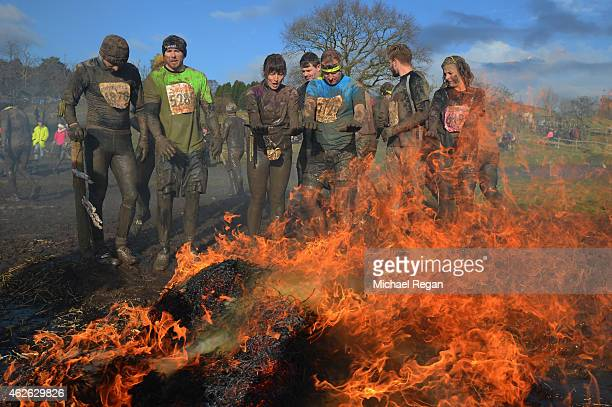 Competitors warm themselves by a fire during the annual Tough Guy Challenge race on February 1 2015 in Telford England