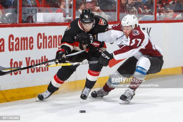 Compher of the Colorado Avalanche battles for the puck against Chris Wideman of the Ottawa Senators during an NHL game at Canadian Tire Centre on...