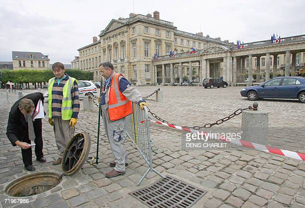 Workers check a sewer opening 22 September 2006 in front of the northern Paris Compiegne castle on the eve of a summit between French President...