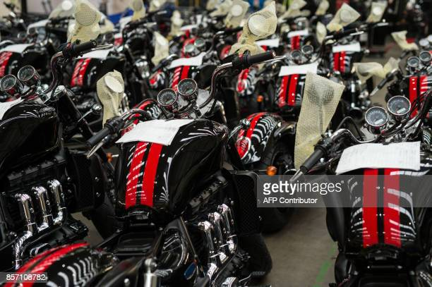 Completed motorcycles are parked adjacent to the assembly line at the Triumph Motorcycles factory in Hinckley central England on October 2 2017...