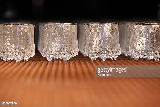 Completed Ultima thule style glasses move along a conveyor belt at the Iittala Oyj glass factory operated by Fiskars Oyj in Hameenlinna Finland on...